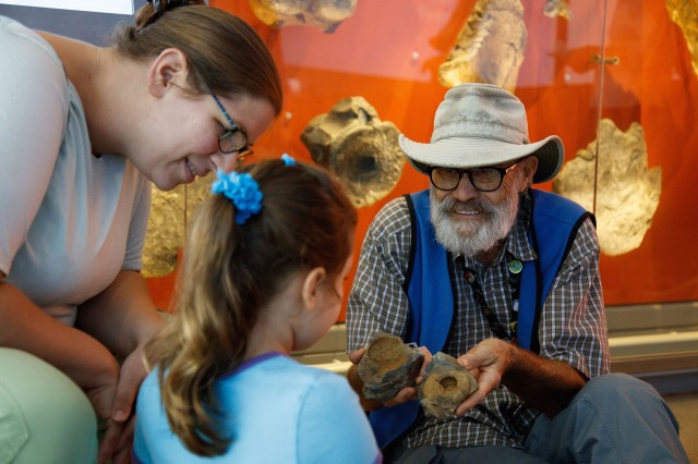 Volunteer with visitors holding fossils