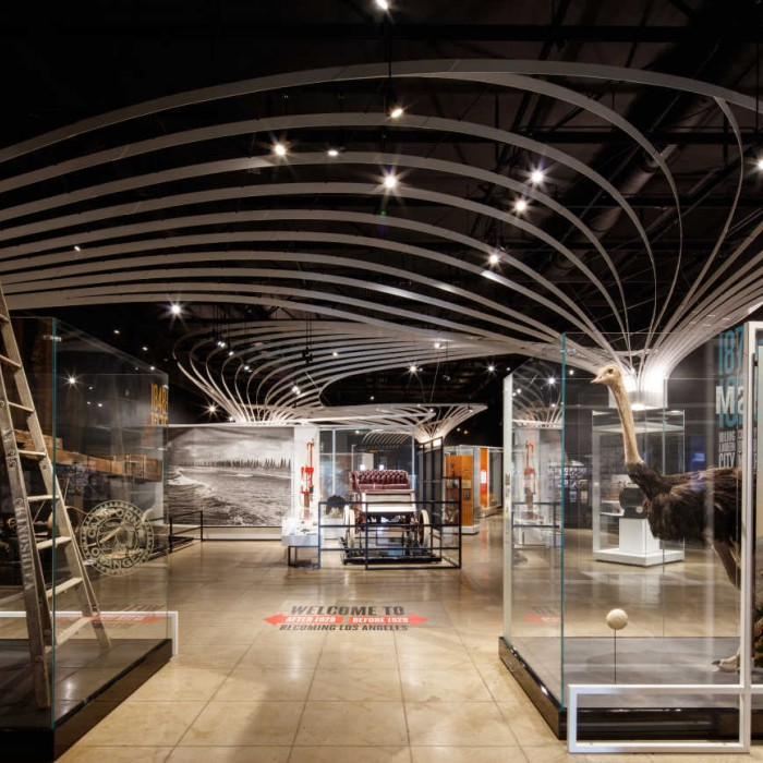 View showing the whole gallery of the Becoming Los Angeles exhibition with glass cases filled with historic objects