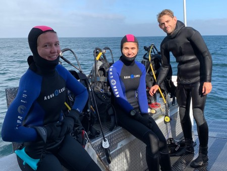 Three divers on boat in August as they prepare to dive for marine specimens.